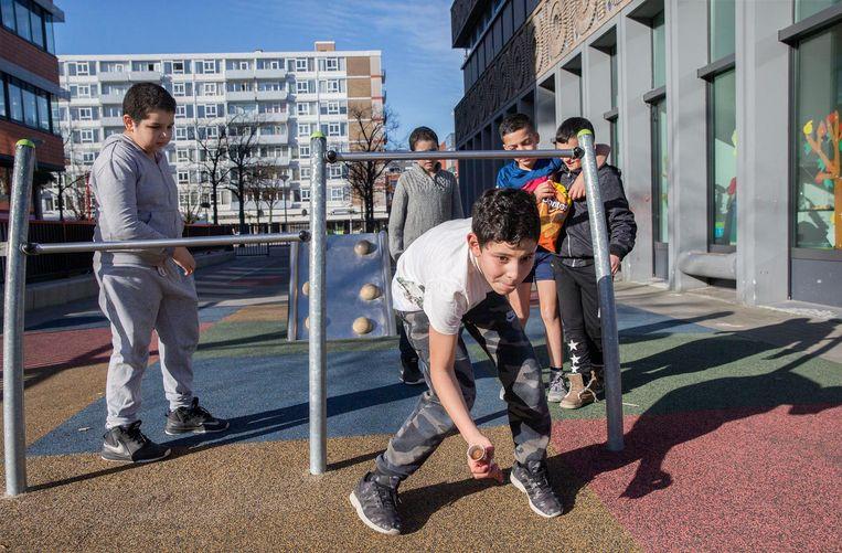 Rond het opgeknapte August Allebéplein in Overtoomse Veld hollen jongens met een voetbal, Calippo's in de aanslag Beeld Jean-Pierre Jans