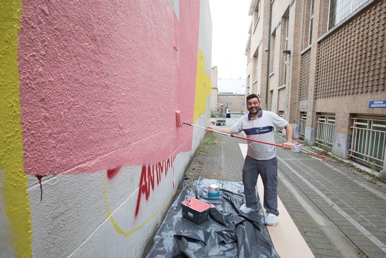 Een van de jongeren schildert een flink stuk muur roze.