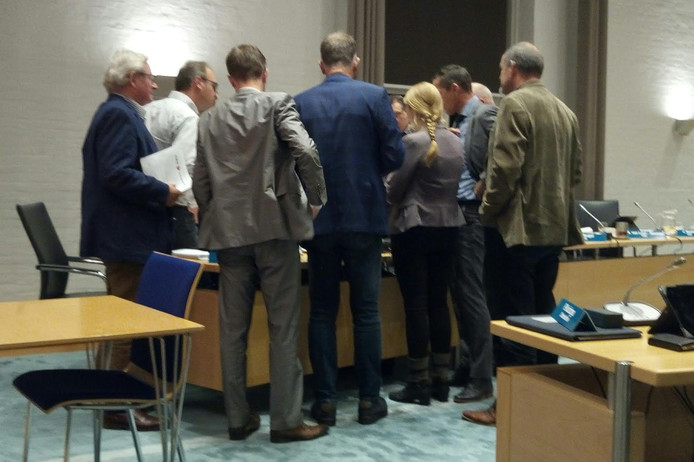 Druk overleg tussen de Kapelse fracties tijdens de schorsing van de gemeenteraadsvergadering.