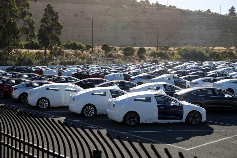 Nieuwe Tesla Models 3 staan op een parkeerplaats in Richmond, Californië te wachten op transport naar klanten.  Beeld REUTERS