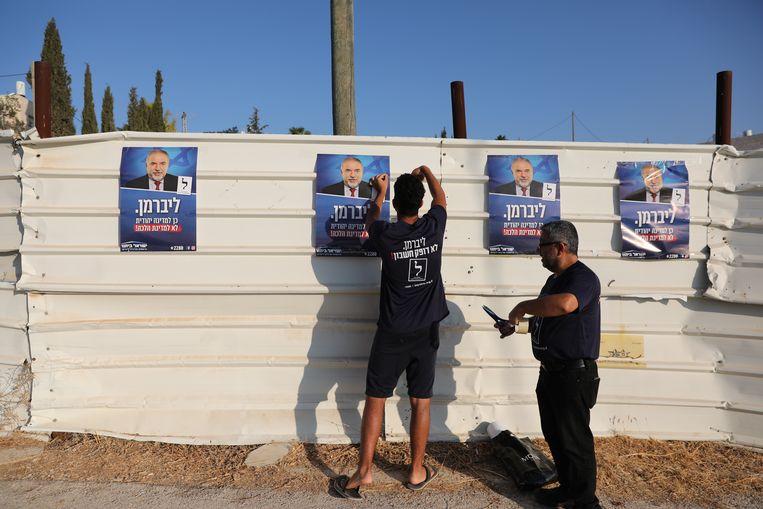 De partij van Avigdor Lieberman, Yisrael Beitenu neemt een sleutelpositie in bij de vorming van een nieuwe regering in Israël. Voor de gang naar de stembus plakten partijleden nog ijverig affiches voor hun partij.  Beeld EPA/ABIR SULTAN