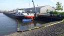 Rond de drugsboot in Moerdijk ligt een scherm in het water. Dit moet voorkomen dat chemicaliën zich verder verspreiden.