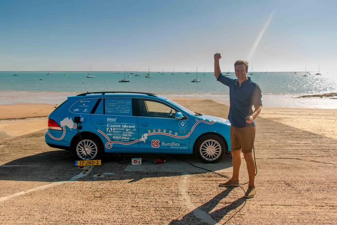 Wiebe Wakker poseert trots in Australië met zijn elektrische auto, na een geslaagde wereldreis.