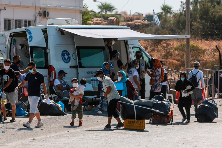 Berooide vluchtelingen trekken naar het nieuwe tijdelijke kamp op Lesbos.  Beeld AFP