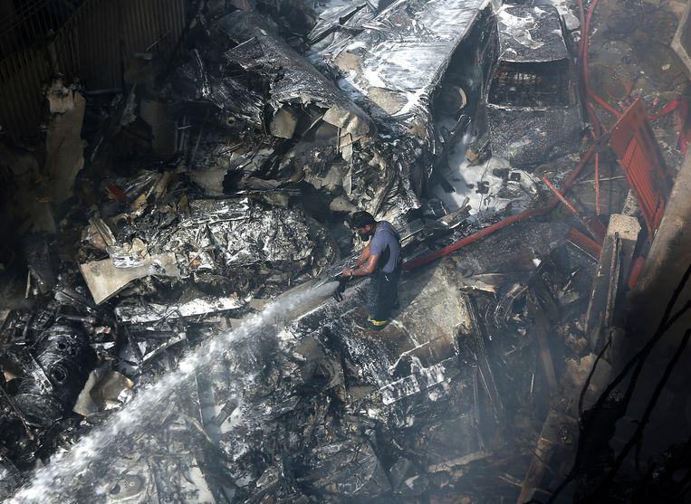 Een brandweerman blust op de brokstukken veroorzaakt door de crash in een woonwijk van Karachi. Beeld AP