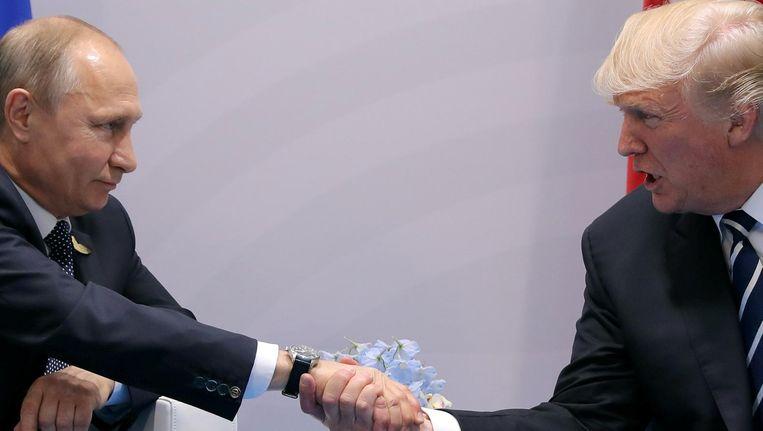De handdruk van het afgelopen jaar van Poetin en Trump, in Hamburg tijdens de G20-top in juli. Beeld Carlos Barria/Reuters