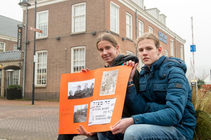 Leerlingen van het Vechtdal College Wouter Neeft (l.) en Tiemen Post vertellen op Holocaust Memorial Day in Ommen aan de hand van een eigen gemaakte poster over de Joodse familie Vomberg die aan de Markt 5 (achtergrond) woonde.