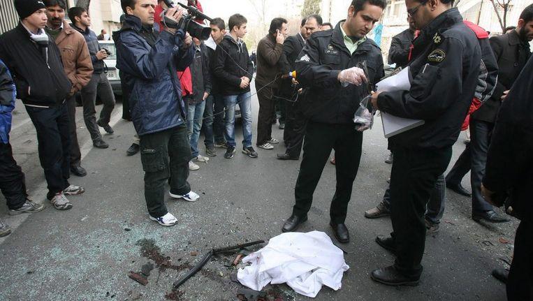 Iraanse agenten doen onderzoek op de plek waar een aanslag is gepleegd op een kernfysicus. Beeld epa