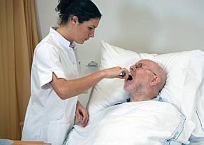 Een verpleegkundigen helpt een patiënt met tanden poetsen