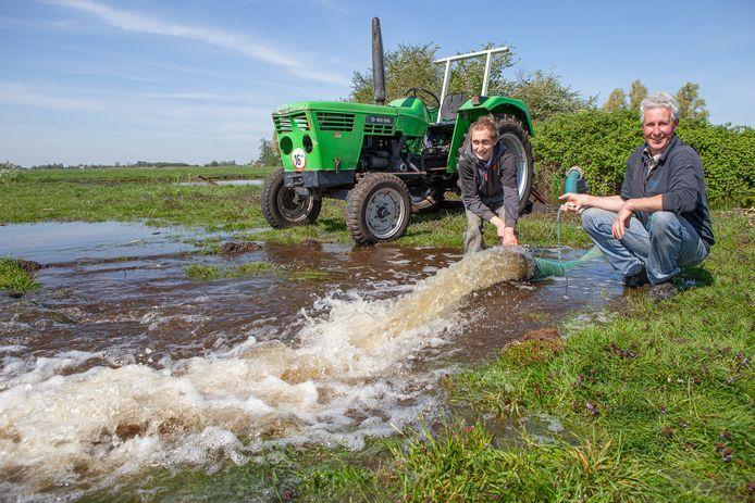 Pieter Versteegh (links) en Dick van der Horst pompen water op het land voor het creëren van plasdrasgebied.