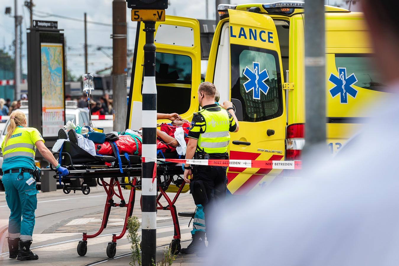 Een van de gewonden wordt naar de ambulance gebracht na de aanslag door een Afghaanse man op Amsterdam Centraal.