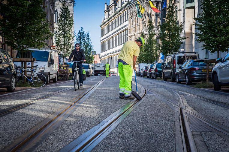 In de Belfortstraat neemt een stadswerker de tramsporen onder handen.