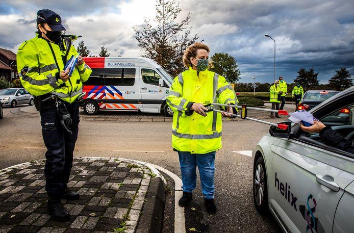 Buurtpreventie en Politie flyeren coronaproof op de Sportlaan in Puttershoek.
