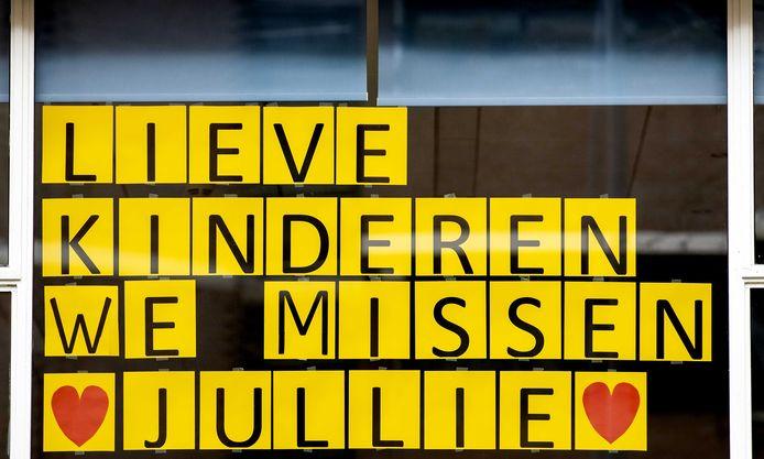 De tekst 'Lieve kinderen we missen jullie' hangt voor een raam bij een school in Rotterdam. De scholen zijn tot minstens 28 april gesloten, als een van de maatregelen omtrent het coronavirus.