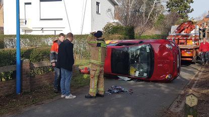 Auto belandt op zijkant door ongeval, brandweer bevrijdt bestuurster