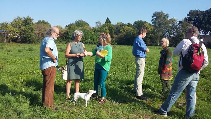 Leden van Vereniging Duurzaam Wonen Overbetuwe (DWO) geven belangstellenden een rondleiding op de beoogde bouwlocatie aan de Veldstraat in Zetten.