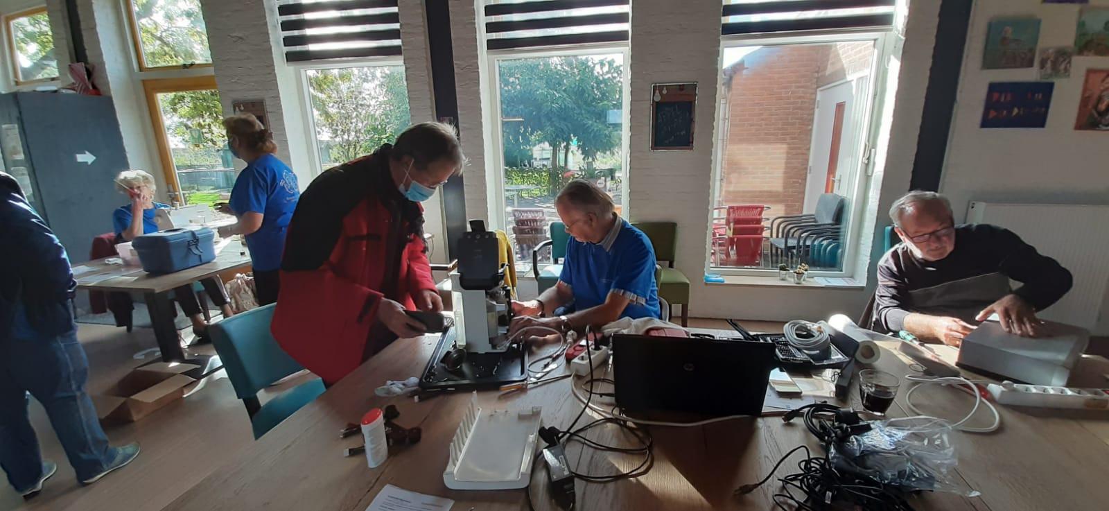 """Adrie de Bruine uit Nieuwerkerk (links) laat een koffiezetapparaat nakijken bij het Repair Café Zierikzee. ,,Zonde om 'm weg te gooien. Het ding ziet er nog keurig uit. Ik hou er niet zo van om zomaar iets weg te gooien."""""""