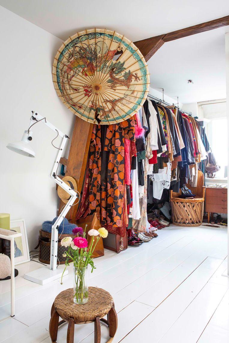 'Waar mijn kleding hangt, was vroeger een piepklein keukentje. De papieren parasol komt van de kringloop.' Beeld Henny van Belkom