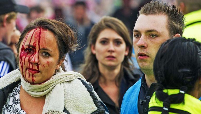 Een vrouw met een hoofdwond op het Museumplein. Tijdens de huldiging van de Ajax-selectie voor het behalen van de dertigste landstitel zijn gewonden gevallen als gevolg van de drukte. Foto Beeld anp