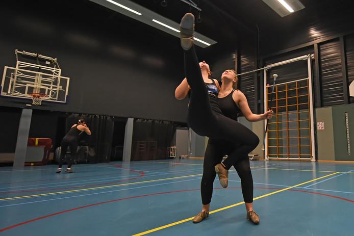 Kyra van Aert en Elvira Oomen van Glitters Dance & Twirlvereniging Prinsenbeek doen een moeilijke oefening met de baton.