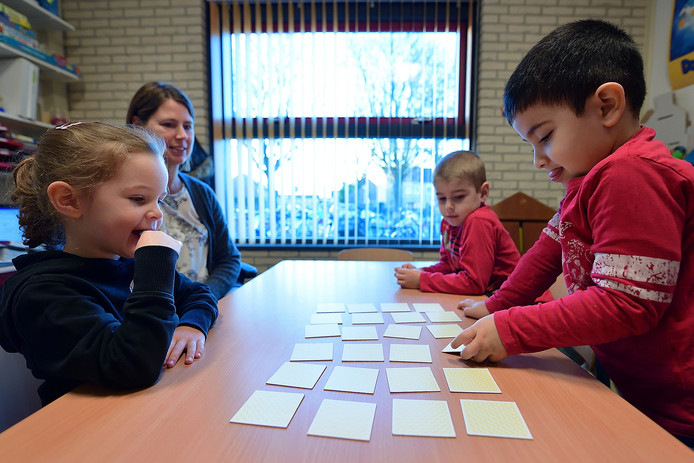 Juf Esther van Deurse speelt op de Gummarusschool in Steenbergen een geheugenspel met de Poolse kleuters Mia en Lucas en de Syrische jongen Ibrahim.