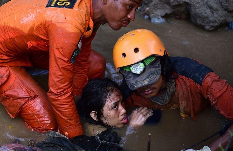 Reddingswerkers redden een vijftienjarig meisje uit haar ondergelopen huis.
