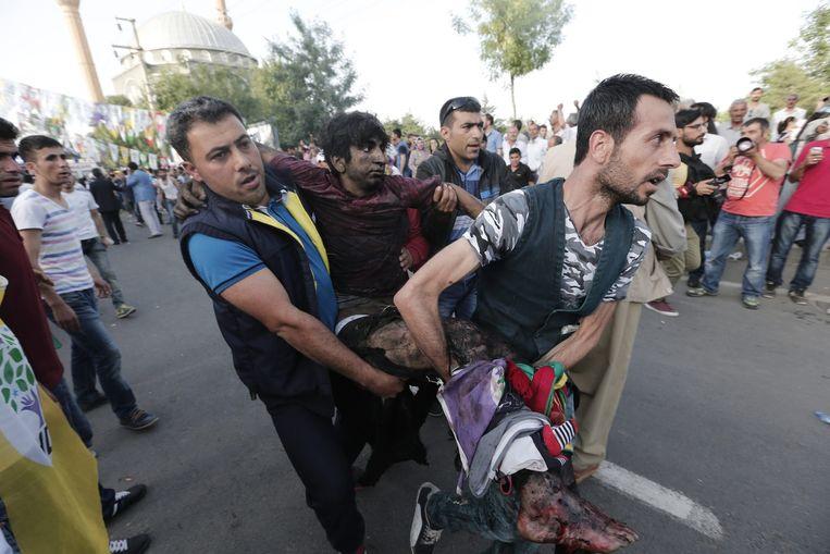 Mensen dragen een man die gewond raakte bij de dubbele aanslag gisteren in Diyarbakir.