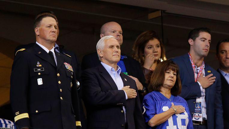 Mike Pence en zijn vrouw staan met hun hand op het hart tijdens het volkslied bij aanvang van de wedstrijd. Beeld ap