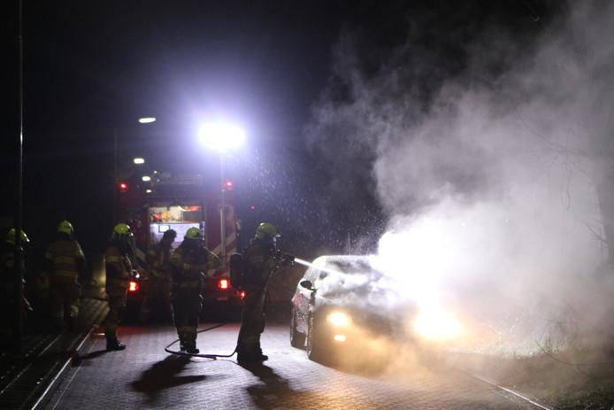 De brandweer blust de brandende wagen in Ede.