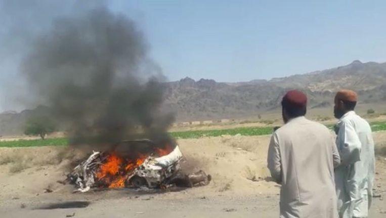 Pakistanen kijken naar het brandende wrak van de auto die met drones is aangevallen. In de wagen zouden een chauffeur en de leider van de Afghaanse Taliban hebben gezeten. Beeld epa