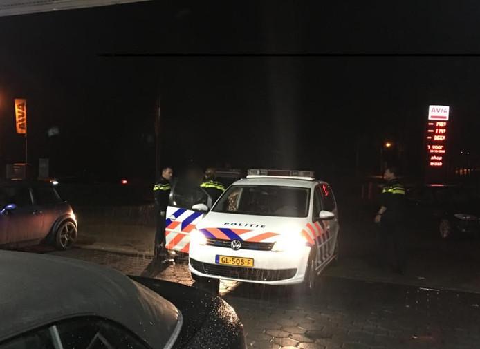De politie pakt een van de verdachten. Op de voorgrond de auto van Verwijs. Links een auto van de verdachten.