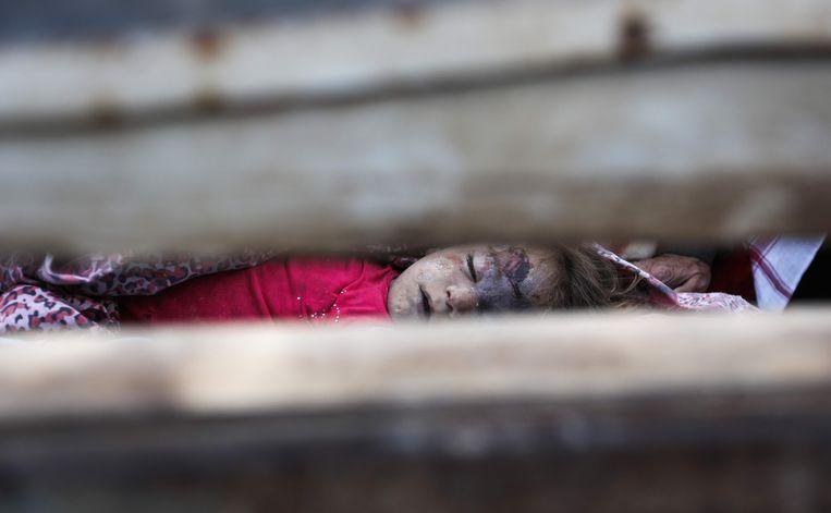 Kinderlijkjes liggen opeengestapeld in een vrachtwagen. Zestien kinderen kwamen om het leven bij de luchtaanval.