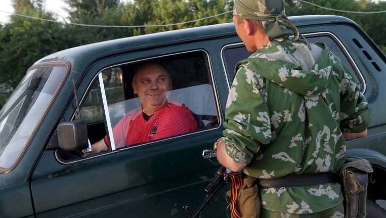 Een gewapende pro-Russische militant spreekt met een bestuurder nabij de grens tussen Rusland en Oekraïne. Beeld afp