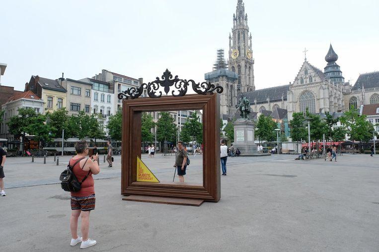 Toeristen nemen een foto met Rubens en de katherdraal.