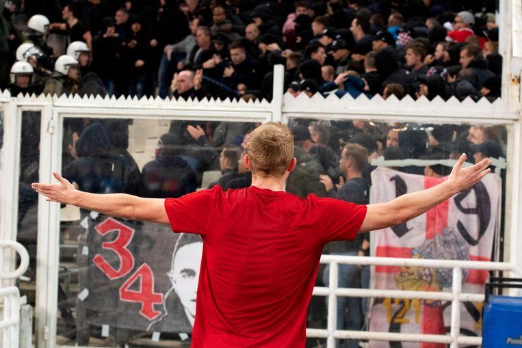 Matthijs de Ligt van Ajax probeert rust te brengen bij de supporters die slaags raakten. Beeld anp