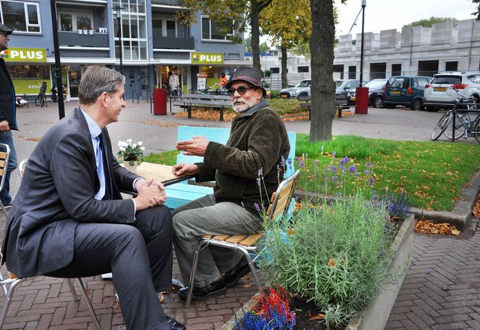 Burgemeester Kolff in gesprek met een bezoeker van het koffienest op het Vogelplein. Een sociaal initiatief vlakbij de Havikstraat, waarvan de nieuwbouw op de achtergrond te zien is. Wethouder Stam prees het Vogelnest. ,,Het zijn kleine stapjes die de stad nodig heeft'', vindt hij.