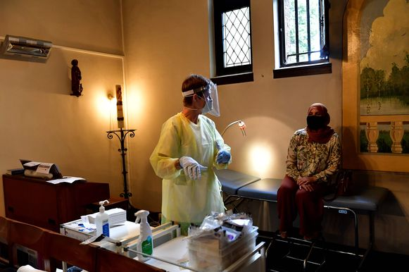Een verpleegster van Geneeskunde voor het Volk maakt zich klaar om een coronatest af te nemen bij een patiënte van de groepspraktijk. De ruimte is bijzonder: de kapel van de Sint-Rochuskerk.