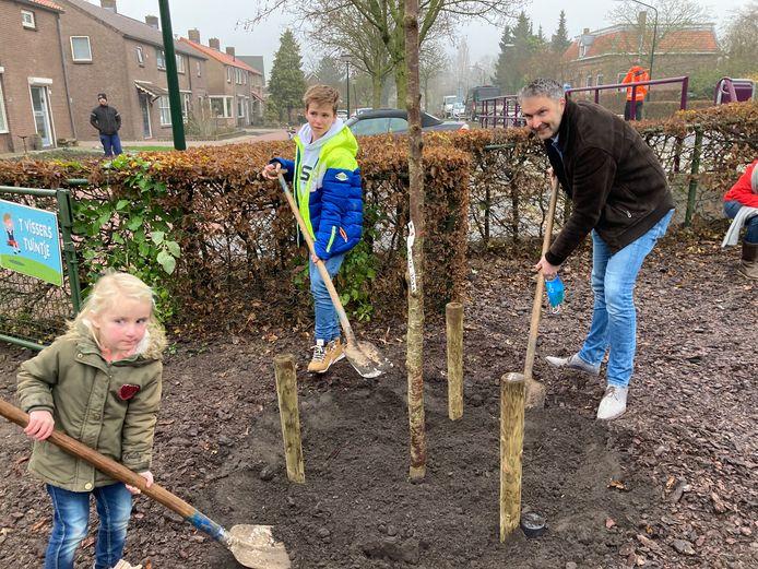 De 4-jarige Pien Uithoven en de 11-jarige Jorey Schellekens helpen wethouder Roland van Vugt met het planten van een boom in Babyloniënbroek