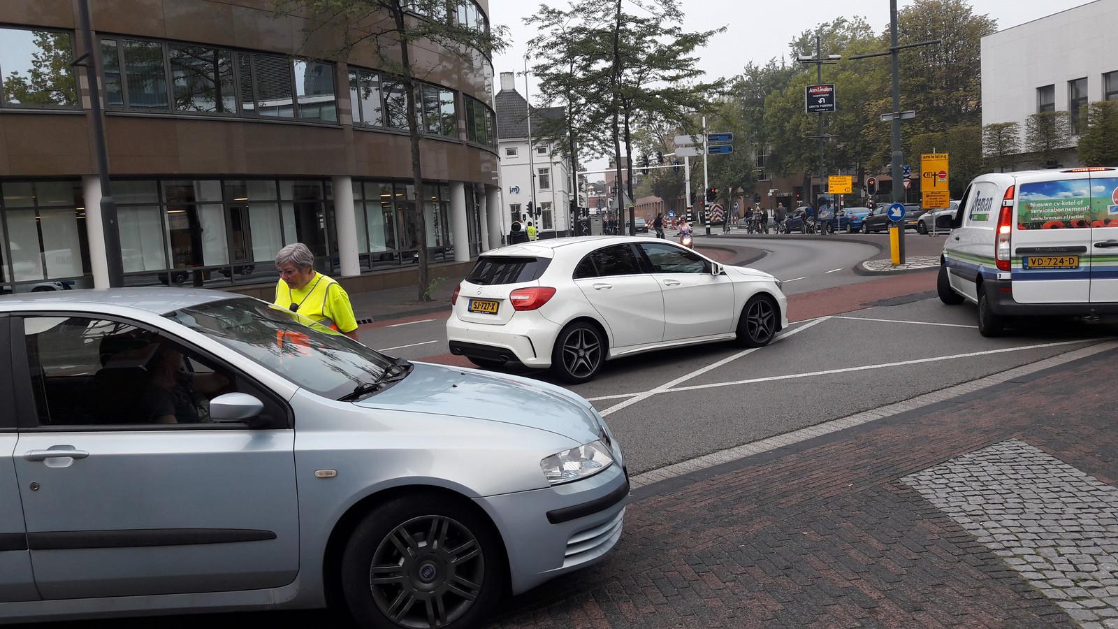 Op de kruising Tramstraat-Kanaalstraat in Eindhoven worden automobilisten aangesproken om het sluipverkeer eruit te halen.