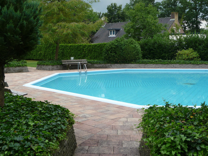 Het zwembad van Dennenoord met daarachter de voormalige bedrijfswoning.
