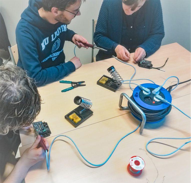 Een groep inwoners is samen met onderzoekers van Odisee aan de slag om sensoren in elkaar te steken tijdens een workshop.