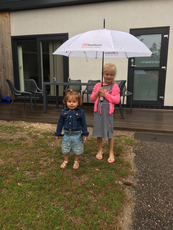 Zusjes Suus (1) en Roos (5) van der Louw op vakantie met opa en oma. Ze hadden geen last van de regen.