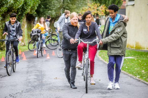 Leerlingen en leerkrachten van Athena, campus Pegasus, leren OKAN-leerlingen fietsen.