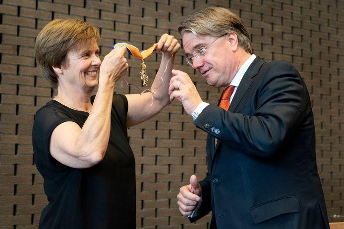 De hoogste onderscheiding voor commissaris van de Koning  Wim van der Donk uit handen van minister Kasja Ollongren. Zijn vrouw spelde de versierselen om vanwege de corona-afstand.
