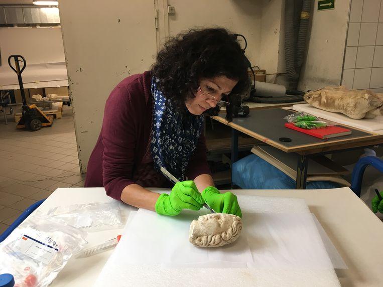 Een microbiologe zoekt naar sporen die de geschiedenis van een van de gesmokkelde beelden verraden. Beeld Universiteit voor Bodemcultuur, Wenen