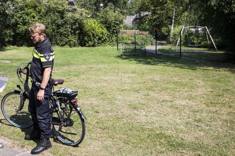 Een  wijkagent bij de speeltuin in de Assense wijk Peelo.