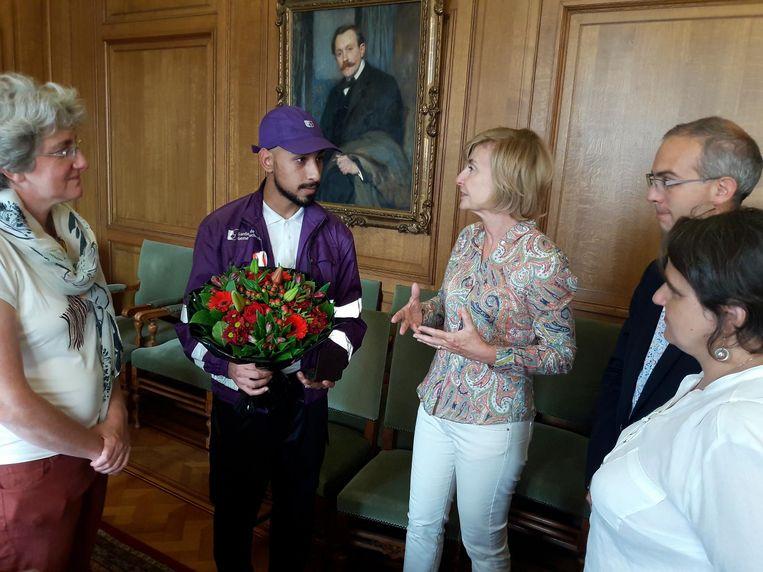 De held van Molenbeek krijgt een bos bloemen overhandigd van burgemeester Schepmans.