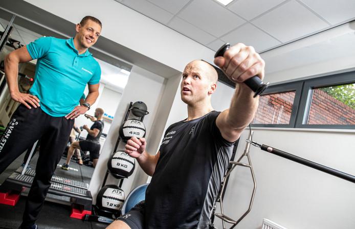 Timothy Petersen werkt zich in het zweet in het krachthonk, onder het toeziend oog van fysiotherapeut Martijn van Strien.
