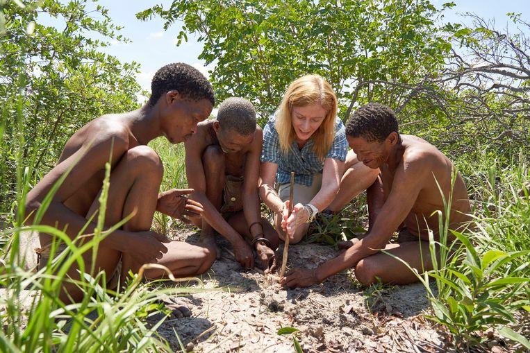 Onderzoeker Vanessa Hayes leert van Ju'Hoansi, een jagersvolk dat leeft in de Kalahari in Namibië, hoe ze vuur moet maken.   Beeld Chris Bennett