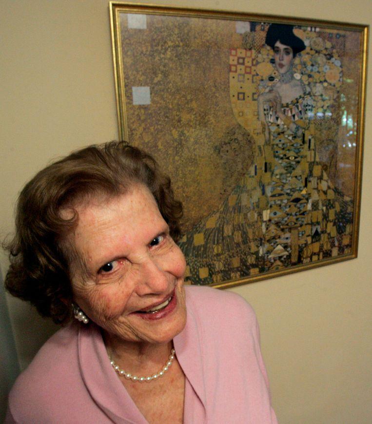 Maria Altmann poseert voor de foto bij het portret van haar tante Adele Bloch-Bauer, van de hand van Gustav Klimt.